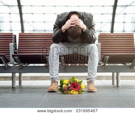 Sad Man Is Sitting Alone At The Train Station With His Head Down