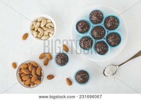 Healthy Chocolate Energy Bites With Nuts, Dates, Cocoa Powder, Coconut Flakes On White Table.