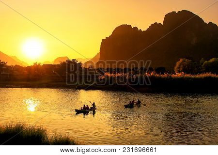 Nam Song River At Sunset With Silhouetted Rock Formations And Kayakers In Vang Vieng, Laos. Vang Vie