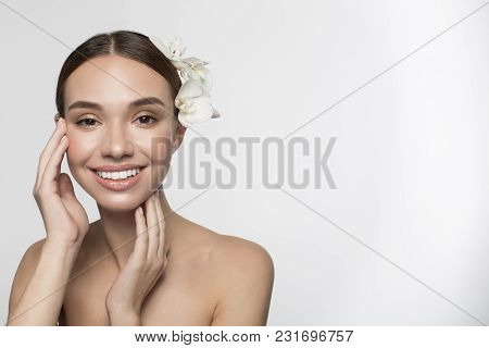 Skincare And Beauty Concept. Satisfied Young Woman With Flower In Hair Is Feeling Pleasure While Enj