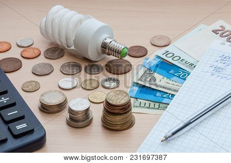 A Light Bulb, A Notebook With A Pen, Bills, Various Money And A Calculator On The Table.