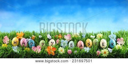 Bright colorful Easter eggs saying Happy Easter on green grass with flowers against blue sky