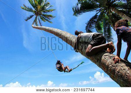 Local Kids Swinging On A Rope Swing In Lavena Village, Taveuni Island, Fiji. Taveuni Is The Third La