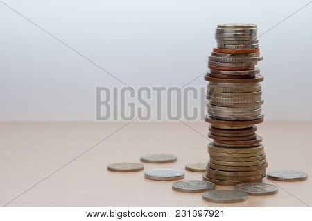 A High Stack Of Coins Of Different Countries, Color, Dignity And Size. Around Her Coins Are Scattere