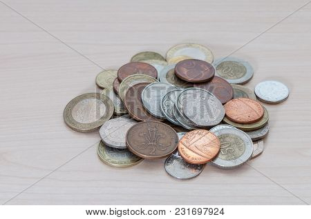 A Handful Of Coins Of Different Countries, Color, Dignity And Size Are Scattered On The Table.