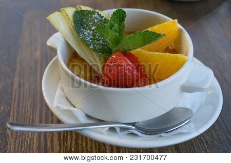 Caramel Dessert With Fresh Fruits In A Snow-white Porcelain Cup On A Wooden Table.