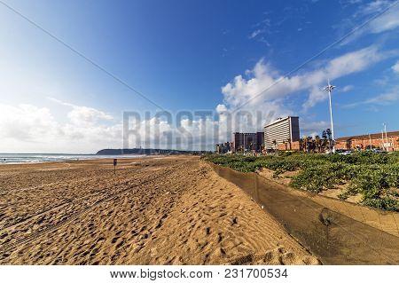 Empty Beach And Dune Vegetation  Against City Coastal Skyline