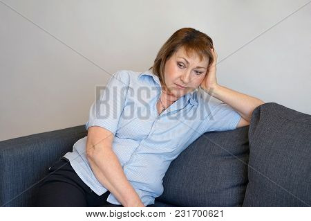 A Lonely Elderly Woman Is Sitting On The Sofa At Home. She Is Depressed And Separated From Problems