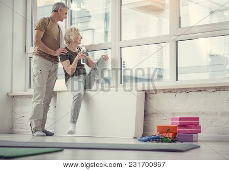 Low Angle Of Joyful Mature Couple Looking Out Of Wide Studio Window And Smiling. Fitness Equipment L