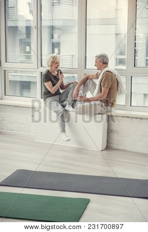 Happy Old Couple Relaxing At Big Studio Window After Training, They Are Talking And Laughing
