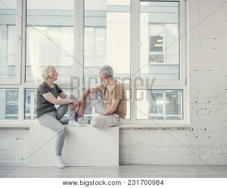 Side View Profile Of Mature Woman And Man Sitting At Wide Studio Window Opposite Each Other. Copy Sp