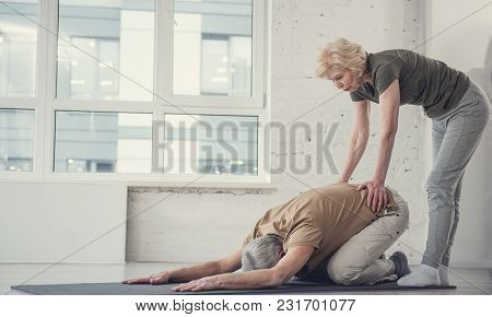 Old Man Lying Face Down On Rug With Legs Tucked Up And Outstretched Arms. Woman Is Helping Him With