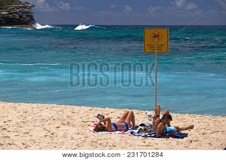 Bronte Beach, Sydney - Nov 9, 2017: Two Sunbathers Pay Scant Attention To The Beach Closed Sign !