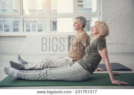 Side View Profile Of Contented Female And Male Pensioners Sitting On Training Carpets And Smiling