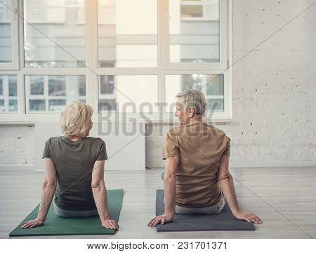 Tranquil Old Male And Woman Sitting With Their Backs On Carpets With Their Back To Camera And Lookin