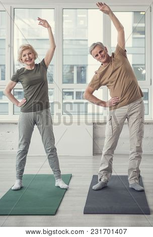 Physical Activity. Full Length Portrait Of Happy Aging Couple Standing On Carpets With Raised Arms.