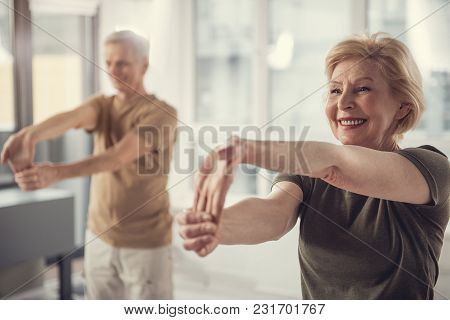 Waist Up Portrait Of Content Mature Female Doing Hand Stretching Exercise. Elderly Man Standing Besi