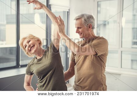 Cheerful Grey Haired Woman Standing With Raised Arm And Smiling, Old Man Beside Her Is Helping With