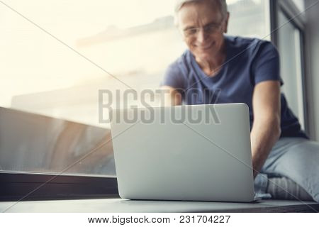 Low Angle Focus On Notebook Located On Windowsill. Old Man Using Gadget On Background. Copy Space In