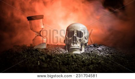 Skull And Vintage Hourglass On Dark Toned Foggy Background Under Beam Of Light. Horror Concept.