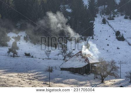 Idyllic Rural Winter Scenery With An Old Wooden House In Fundata Village, Brasov County, Romania.