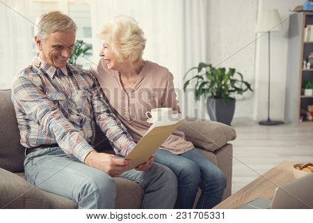 Old Man Resting On Couch And Looking At Documents With Satisfaction. His Glad Wife Sitting With Cup