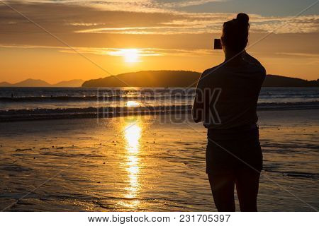 Rear View Of Silhouette Woman Photographing Sunset At Beach