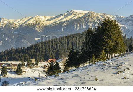 Winter Alpine Scenery With Small Romanian Village In The Valley Of Bucegi Mountains, Fundata Village