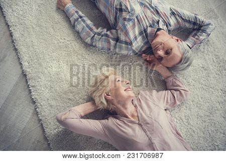 Top View Of Satisfied Senior Couple Resting On Comfortable Rug And Looking At Each Other With Affect