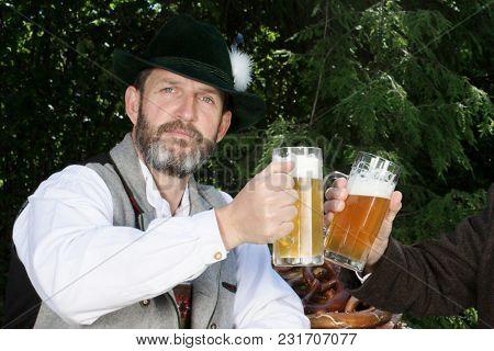Portrait Of Bavarian Man Drinking Beer In Beergarden