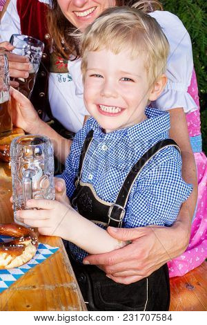Portrait Of Young Bavarian Boy With Family At Beergarden