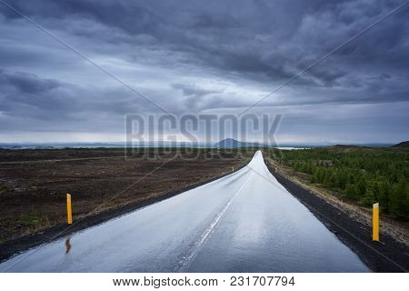 Landscape with a terrible dark stormy sky. Wet road in Iceland. Bad weather. Near Lake Myvatn