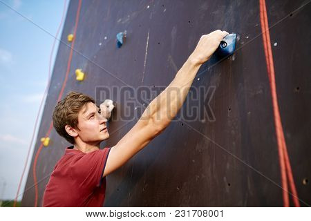 Back View Close-up Of Climber Hands On A Rock Hook Of The Artificial Climbing Wall Outdoors. Young H