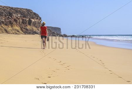Lonely Girl Walking In A Solitary Beach. Image With Many Copy Space Available.