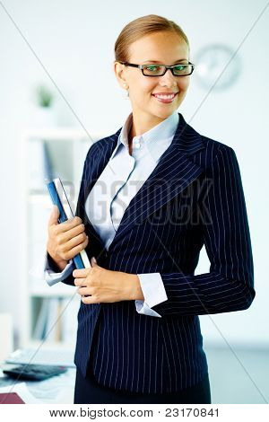 Portrait of elegant businesswoman with handbooks looking at camera