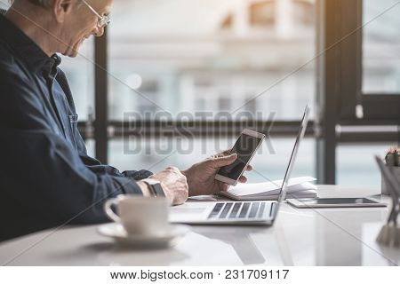 Outgoing Mature Male Looking At Screen Of Mobile While Working With Laptop At Table. Cheerful Employ