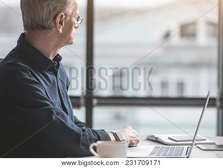 Thoughtful Old Businessman Looking At Window During Job At Desk. Dreaminess During Labor Concept