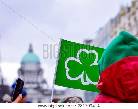 St. Patricks Day 2018 At Belfast City. People Holding Green Flag With Shamrock Symbol In Front Of Be