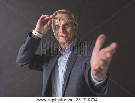Hey You. Portrait Of Smiling Old Businessman Gesticulating Hand While Looking At Camera. Cheerful Em
