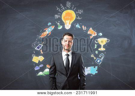 Presentation And Seminar Concept. Portrait Of Handsome European Businessman Standing On Chalkboard W