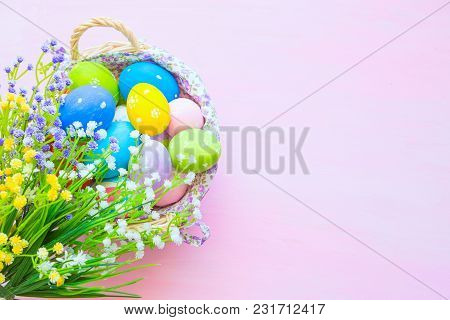 Easter Eggs In Basket On Wooden Pink Table. Top View.