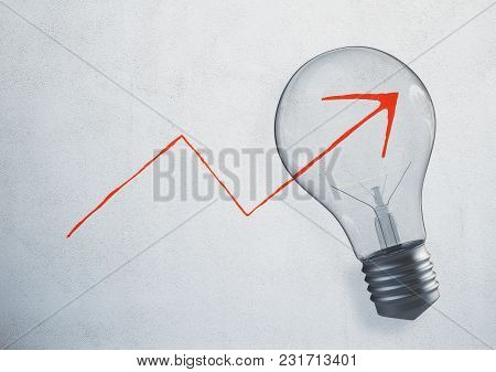 Glowing Light Bulb With Drawn Upward Chart Arrow On Concrete Wall. Finance, Success And Idea Backgro