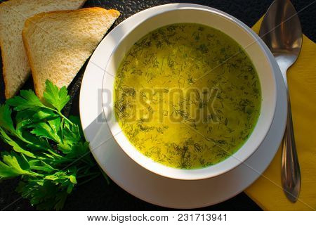 Appetizing Soup From Chicken Yellow Broth On A Black Table With Triangular Bread And Parsley Sprouts