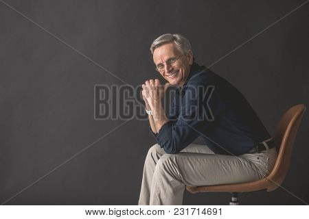 Portrait Of Cheerful Senior Male Resting On Cozy Seat While Looking At Camera. Happy Worker Concept