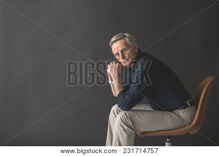 Portrait Of Concentrated Mature Male Looking At Camera While Sitting On Chair. Orderly Employer Conc