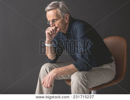Side View Calm Old Man Thinking While Closing Mouth By Arm. He Locating On Seat