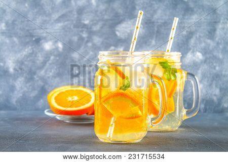 Orange Detox Water In Mason Jars On A Gray Concrete Background. Healthy Food, Drinks