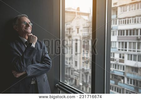 Portrait Of Pensive Senior Employer Looking At Window While Leaning Against Wall Indoor. He Keeping