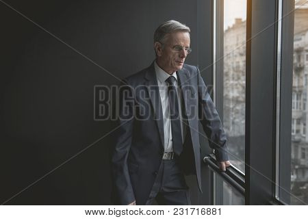 Portrait Of Pensive Senior Male Looking At Window While Situating In Room. Relax And Labor Concept