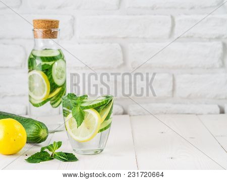 Infused Detox Water With Cucumber, Lemon And Mint In Glass And Bottle On White Table. Diet, Healthy